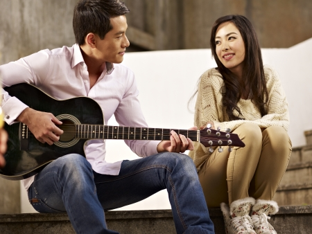 young asian lovers sitting on steps playing guitar and singing Stock Photo