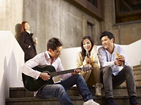young asian friends lovers sitting on steps enjoying beer and music
