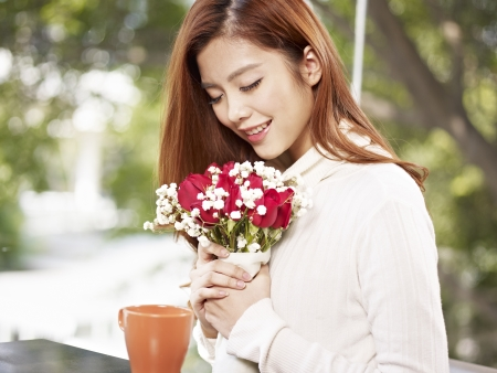 remembering: young asian woman in love holding flowers and smiling, eyes closed, valentine