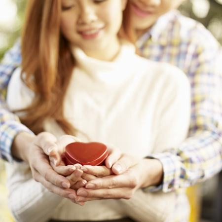 lovers embracing: loving asian couple holding a heart shaped box together, focus on hands  Stock Photo