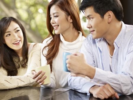 socializando: jóvenes amigos hablando y beber café en la cafetería