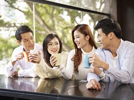 jóvenes amigos hablando y beber café en la cafetería