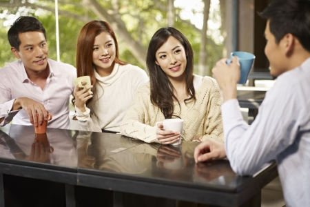 socializing: young friends talking and drinking coffee in cafe  Stock Photo