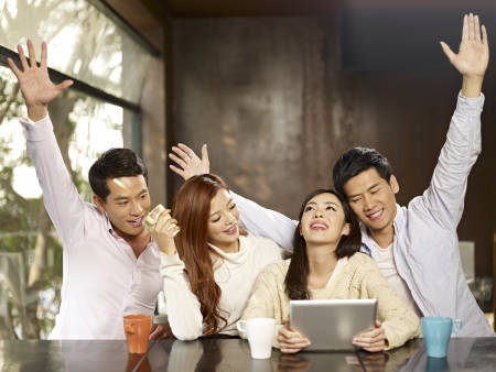 laughing: young people cheering while watching a game on tablet computer  Stock Photo