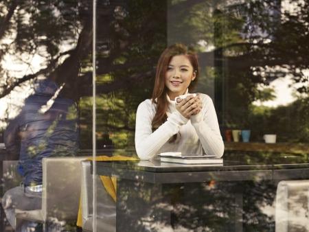 business asia: giovane donna seduta accanto a finestre in cafe Archivio Fotografico