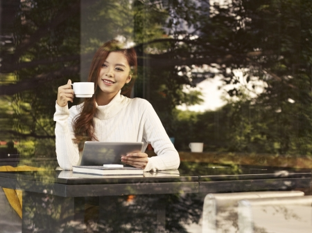 young woman sitting next to windows drinking coffee with tablet computer in hand in cafe