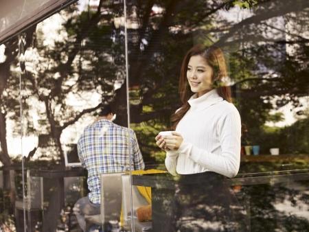 mujer joven de pie delante de las ventanas con la taza de café en la mano en el café Foto de archivo