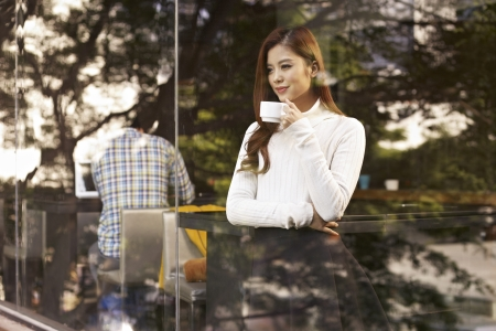 young woman standing in front of windows drinking coffee in cafe  Imagens