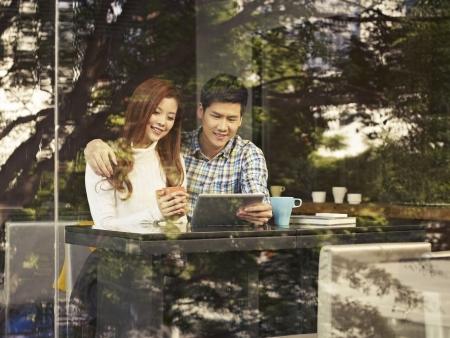 カフェでタブレット コンピューターでの窓の隣に座っていた若いカップル 写真素材