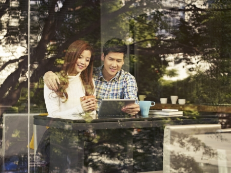 young couple sitting next to windows looking at tablet computer in cafe