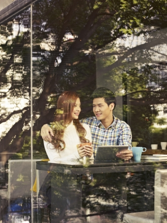 young couple sitting next to windows with tablet computer in cafe  photo