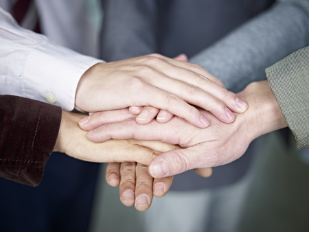 team of businesspeople showing unity by putting hands together  photo