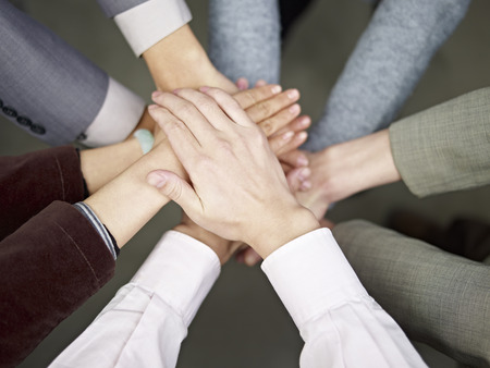 strength in unity: team of businesspeople showing unity by putting hands together  Stock Photo