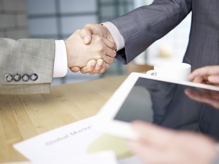 business relationship: business people shaking hands in office  Stock Photo