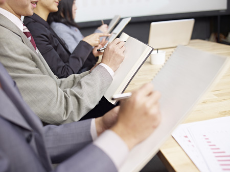 business attire: business people taking notes during meeting