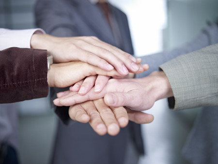 teammates: business people putting hands together to show unity