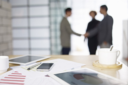 close-up of business items with people meeting in background