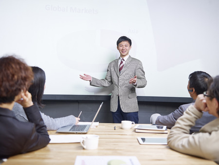 business attire: young man conducting presentation in front of  small group of people