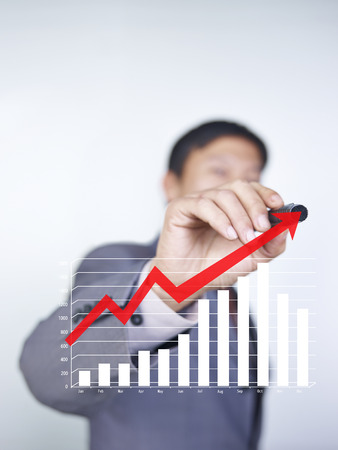sales person: business person drawing an arrow on glass to indicate upward trend in sales Stock Photo