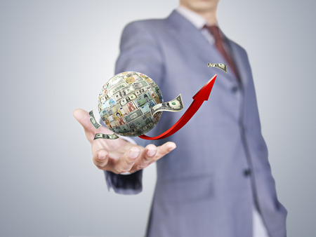 hand of a business person holding the globe covered with different currencies photo