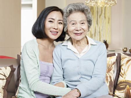 chinese woman: asian mother and adult daughter sitting on couch smiling Stock Photo