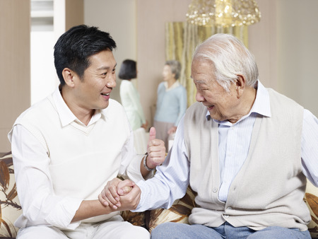 asian father and adult son chatting on couch photo