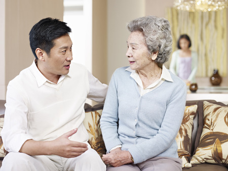 asian mother and adult son chatting on couch Stock Photo