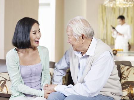 padres hablando con hijos: asiático padre e hija adulta charlando en el sofá Foto de archivo