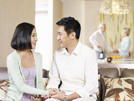 asian couple sitting on couch and looking at each other with their senior parents in the background