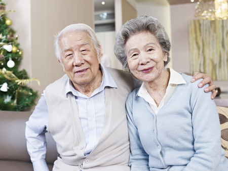 old people: home portrait of senior asian couple smiling