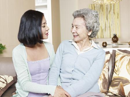 padres hablando con hijos: alto madre asi�tica que charla con la hija adulta en el hogar