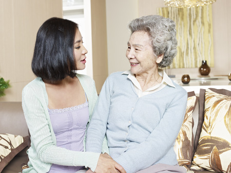 daughter in law: senior asian mother chatting with adult daughter at home