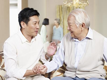 alto padre asiático charlando con el hijo adulto en el hogar