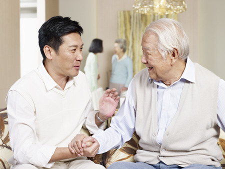 senior asian father chatting with adult son at home