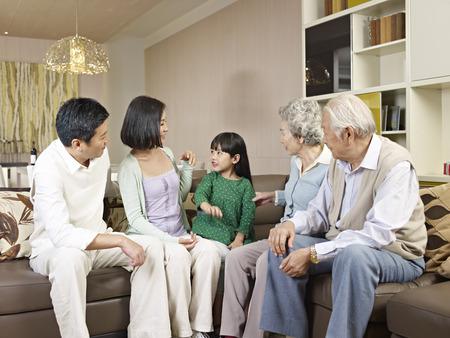 padres hablando con hijos: de tres generaciones de la familia asiática en casa