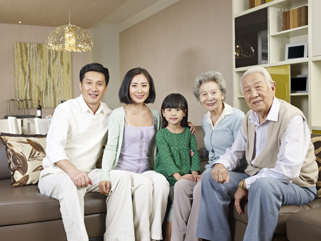 three persons: home portrait of a happy asian family