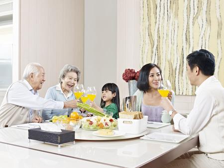 niños desayunando: familia de tres generaciones que tienen comida en casa