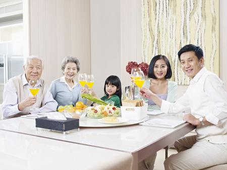 convivencia familiar: familia de tres generaciones que tienen comida en casa
