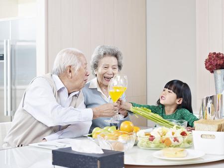 おじいちゃんとおばあちゃんと乾杯の孫娘 写真素材