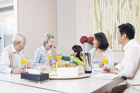 drie-generatie familie die maaltijd thuis Stockfoto