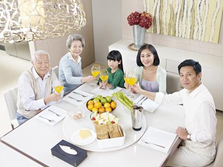 generace: tři generace rodiny s jídlem doma