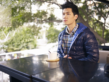 young man waiting for someone in cafe photo