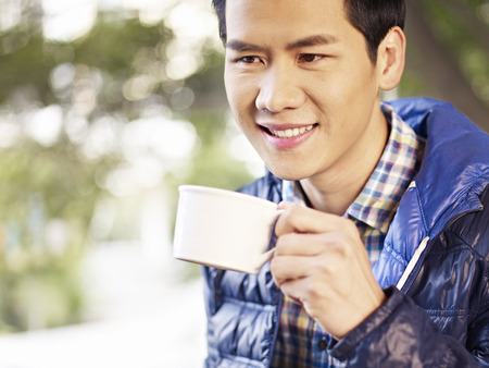 young man holding a coffee cup smiling photo