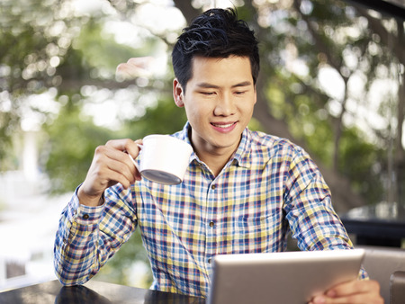 young man looking at tablet computer holding coffee cup smiling photo