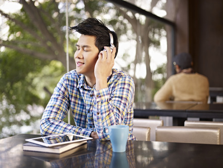 young man wearing headphone enjoying musci in cafe photo