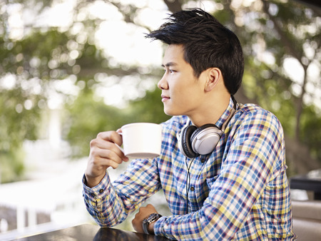 passing: young asian adult man holding coffee cup headphone around neck in cafe
