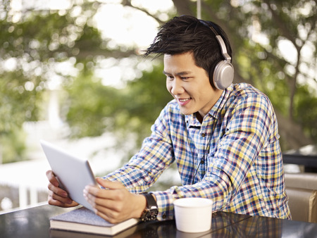 young asian adult man wearing headphone using tablet in cafe