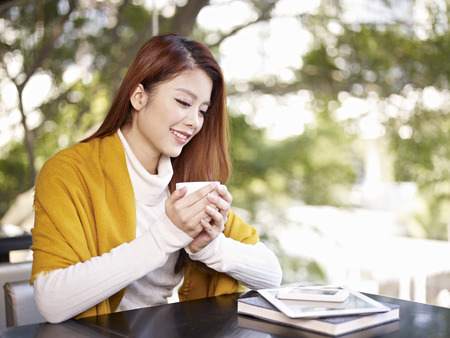 young woman holding coffee cup smiling