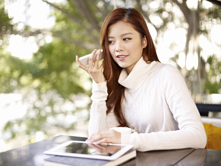 using voice: young woman listening to voice message using mobile phone  Stock Photo