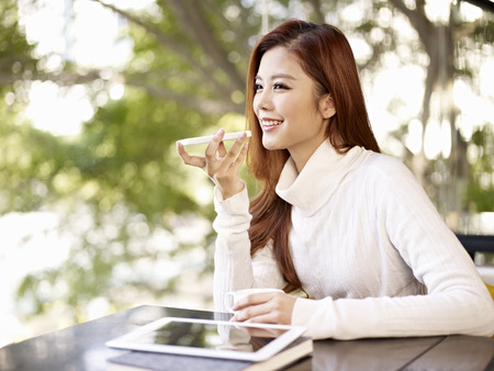 young woman leaving voice message using mobile phone